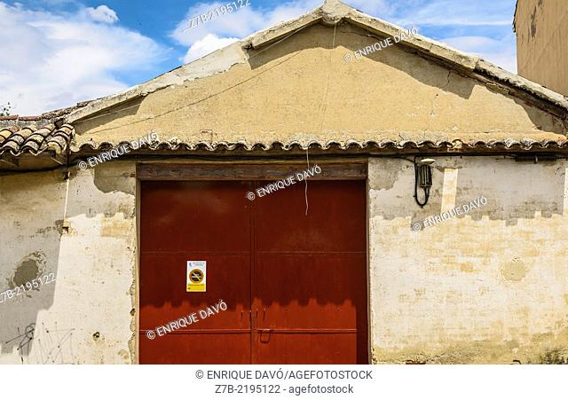 View of an orange gate of a house, Chinchon village, Madrid province, Spain