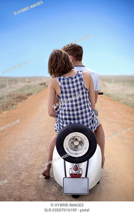 Couple riding scooter together