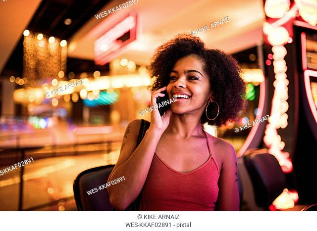 USA, Nevada, Las Vegas, portrait of happy young woman on cell phone in a casino