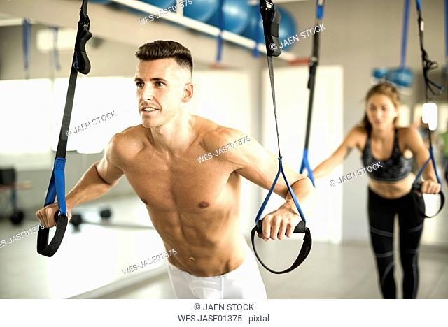 Barechested man and woman doing suspension training in gym