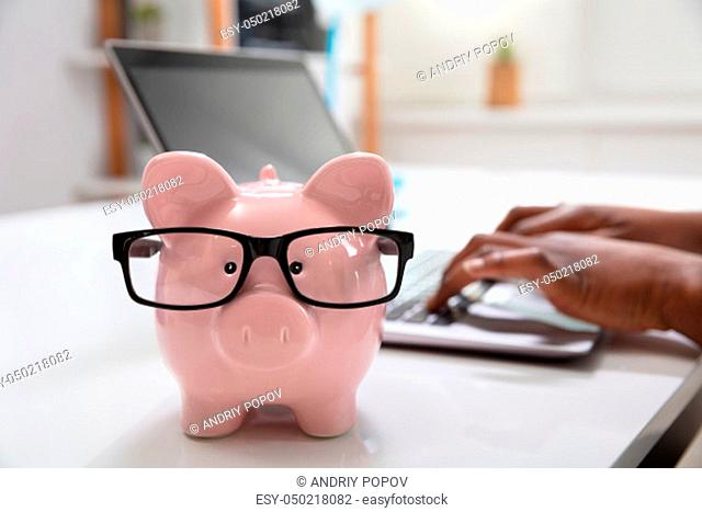 Close-up Of Pink Piggy Bank In Front Of A Business Person Using Laptop At Workplace