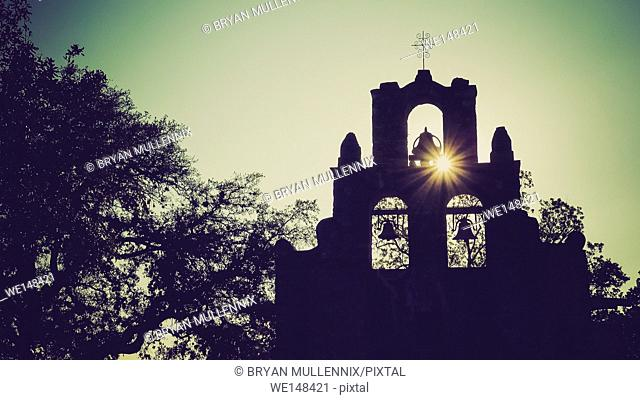 Spanish Mission Espada church bells in silhouette as the sun sets behind mission in San Antonio, Texas