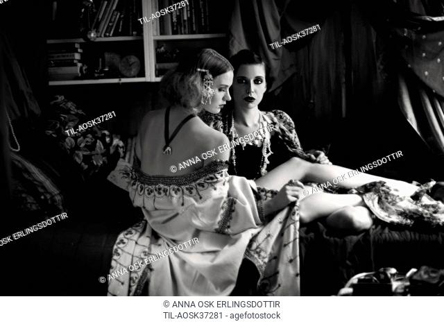 Close up of two young adult females gazing at each other with Bohemian clothing