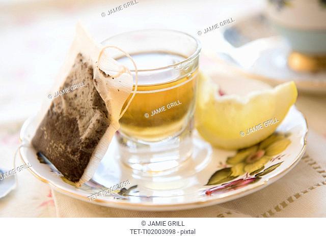 Whiskey in shot glass, slice of lemon and teabag on saucer