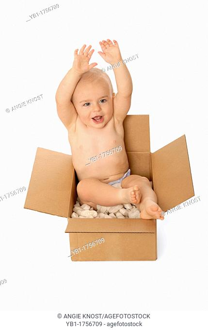 Happy one year old baby boy sitting in a cardboard box, with foam packing peanuts