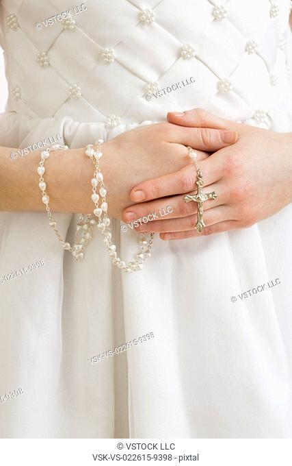 Mid-section of girl (8-9) holding rosary beads