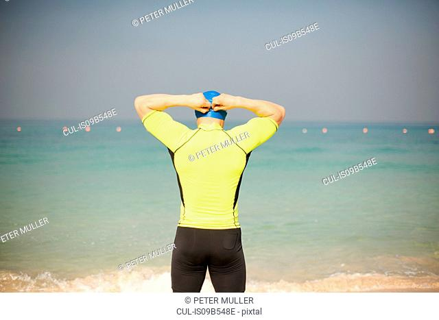 Rear view of mature man adjusting swimming cap on beach, Dubai, United Arab Emirates