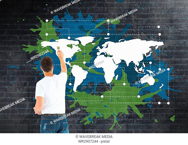 Man painting a Colorful Map with paint splatters on wall background