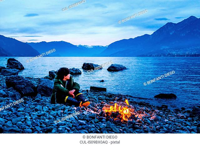 Boy by campfire at dusk, Onno, Lombardy, Italy
