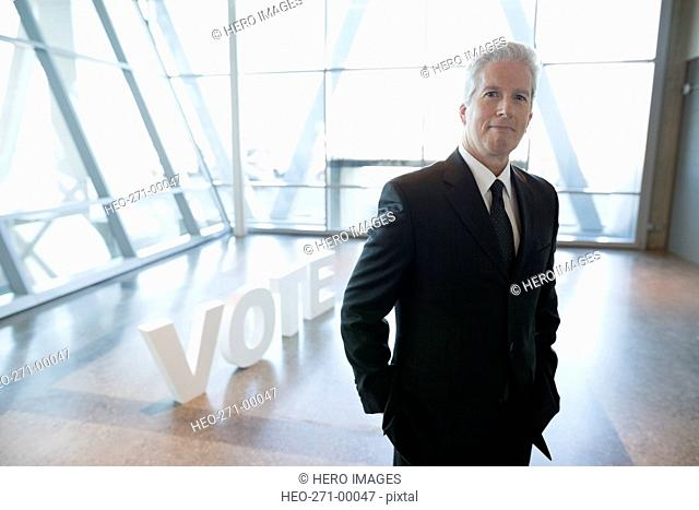 Portrait confident businessman near Vote text