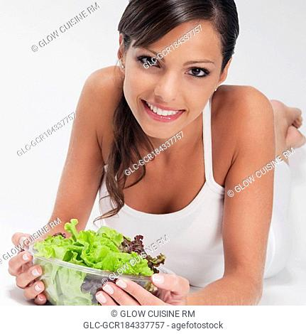 Woman holding a bowl of vegetable salad and smiling