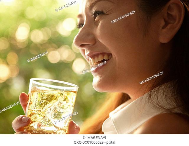 Young woman drinking highball