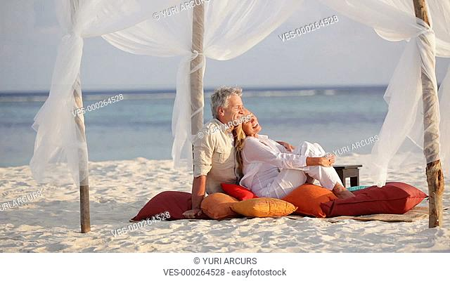 Loving mature couple sitting comfortably on a beach at sunset chatting