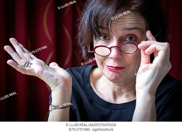 Middle-aged woman with round glasses, with one hand on the glasses and the other in accordance expression