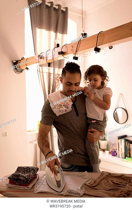Man ironing his cloth while holding her daughter