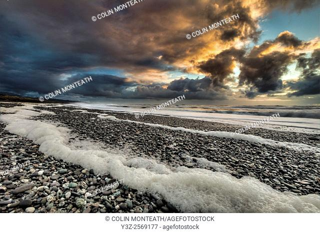 Mananui beach at sunset, storm approaching, sea foam blown up onto beach, near Hokitika, West Coast