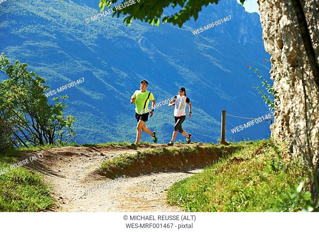 Italy, Trentino, couple running near Lake Garda