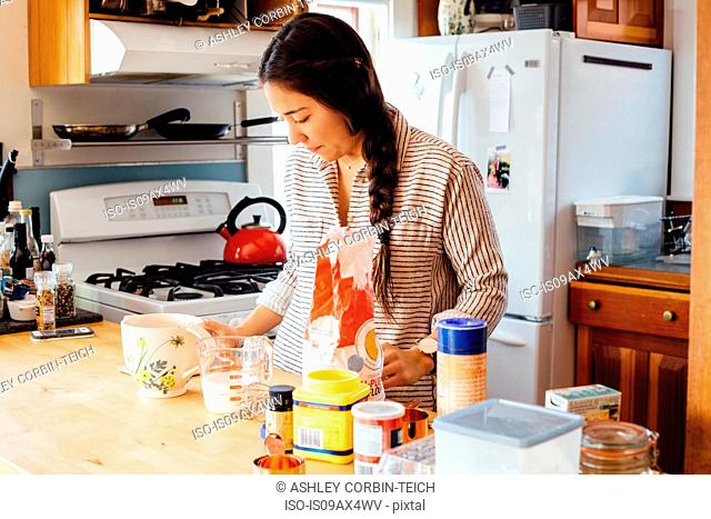 Woman in kitchen preparing waffle batter