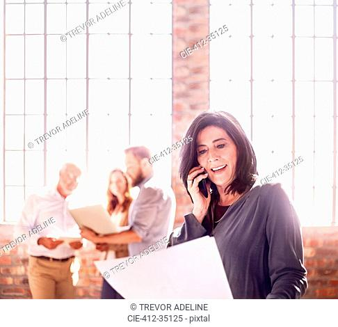 Businesswoman with paperwork talking on cell phone in office