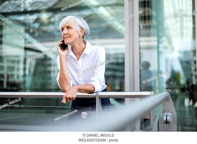 Senior businesswoman leaning on railing in the city talking on cell phone