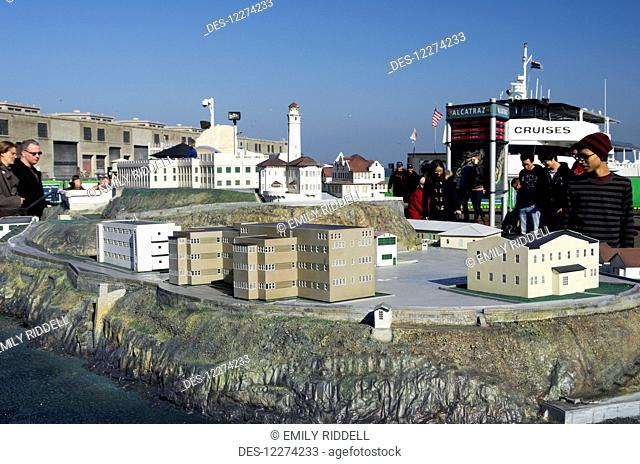 Alcatraz plaza, visitors look at model of the island prison while waiting for the boat; San Francisco, California, United States of America