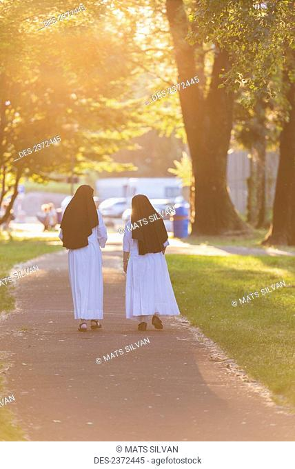 Two Nuns Walk Together Down A Pathway Golden With Sunlight; Locarno, Ticino, Switzerland