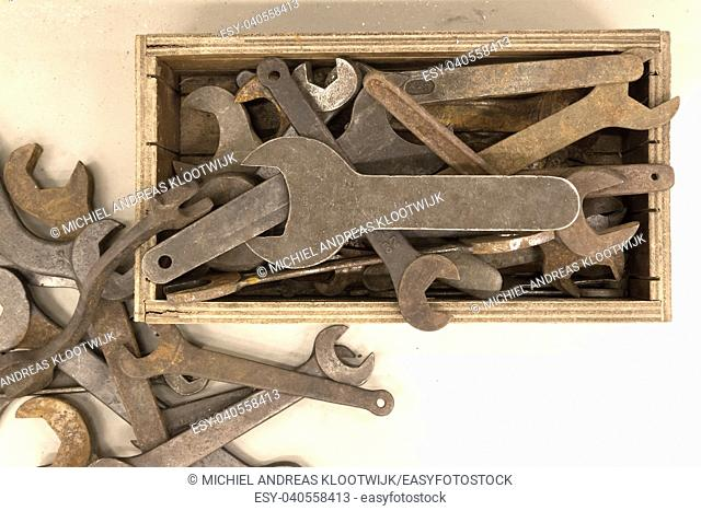 Collection of old rusty wrenches on a dirty floor