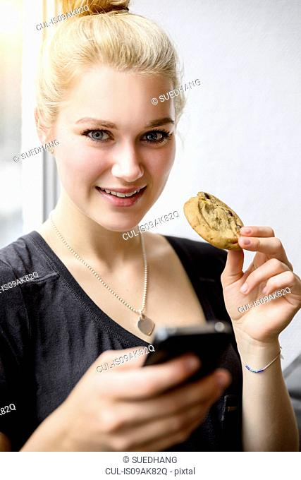 Portrait of young woman using smartphone and eating a biscuit