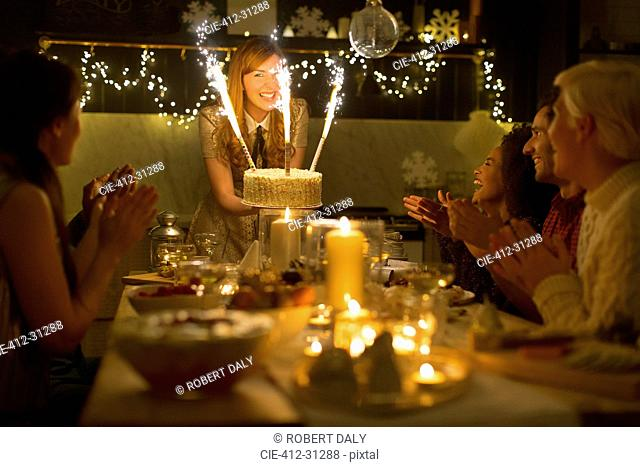 Woman serving Christmas cake with sparkler fireworks to clapping family