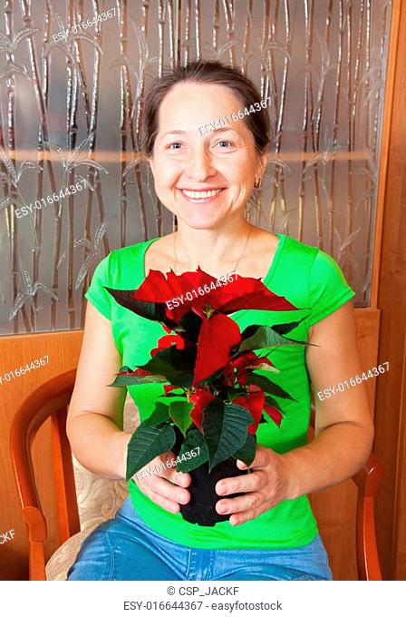 woman with Poinsettia in flowering pot