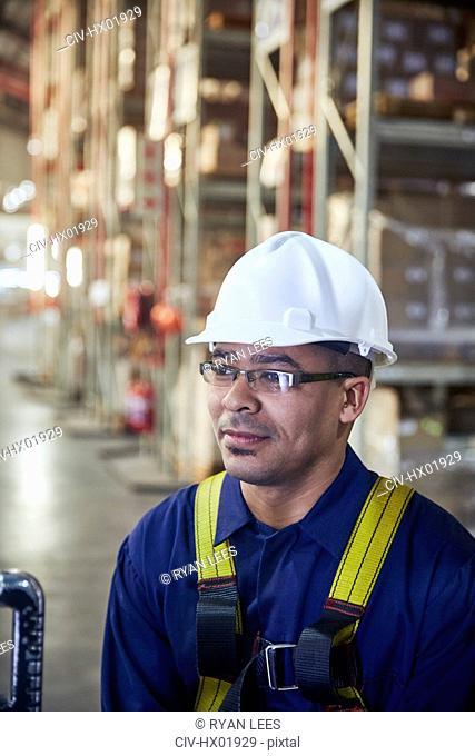 Worker wearing hard-hat looking away in distribution warehouse