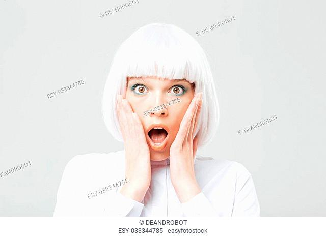 Scared shocked young woman with opened mouth and hands on cheeks