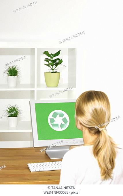 Germany, Woman sitting at computer, rear view, Recycling symbol on screen