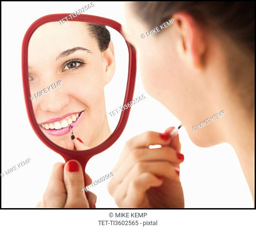Studio portrait of young woman applying lipstick in mirror