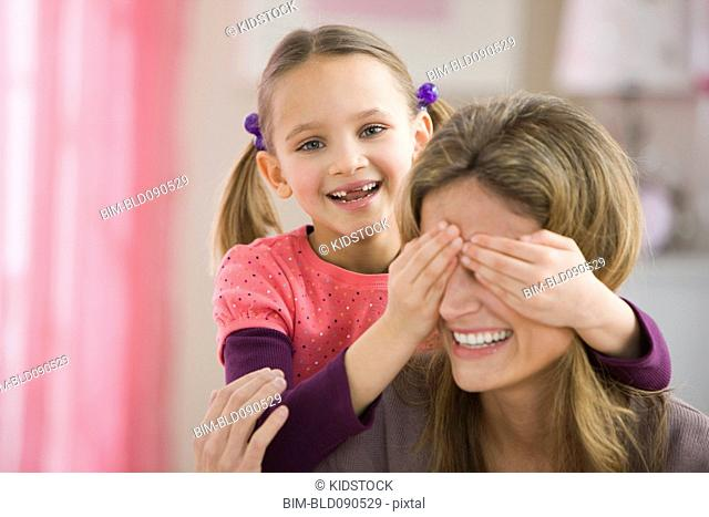Daughter covering mother's eyes