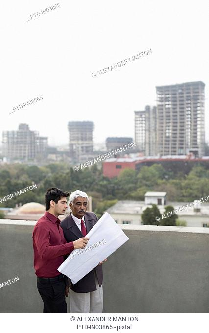 India, Architects and client discussing building plans