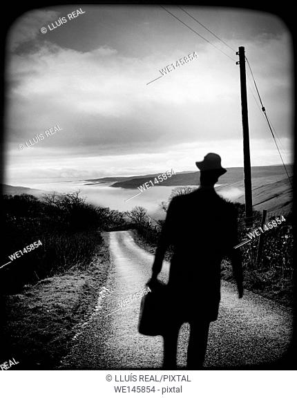 Silhouette of a unrecognizable and incognito man with a executive briefcase walking on a road