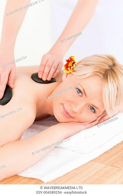 Cute woman receiving a massage with hot stones