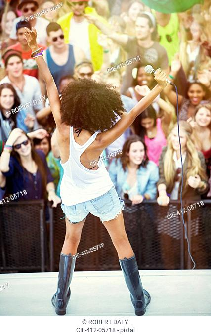 Fans cheering for woman performing on stage