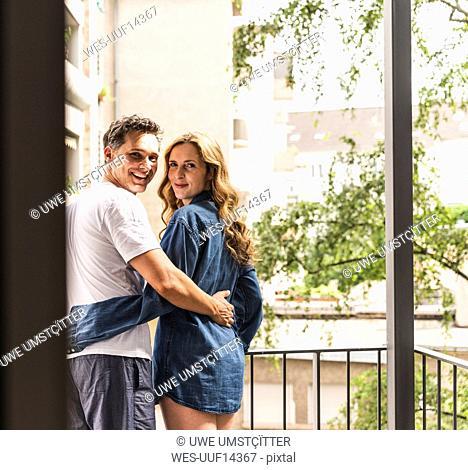 Happy couple in nightwear standing on balcony hugging