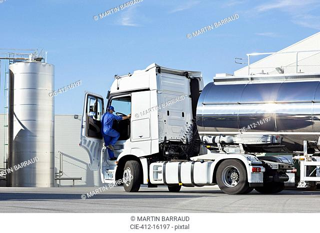 Truck driver climbing into stainless steel milk tanker