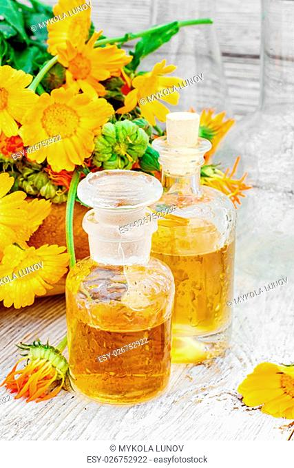 Blooming calendula and jars of prepared medicinal extract