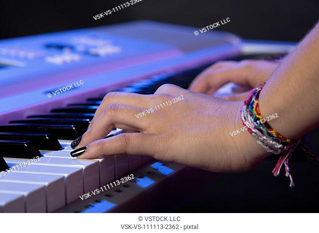 Hands of female musician playing keyboard