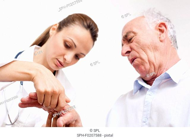 Nurse checking man's hand joints