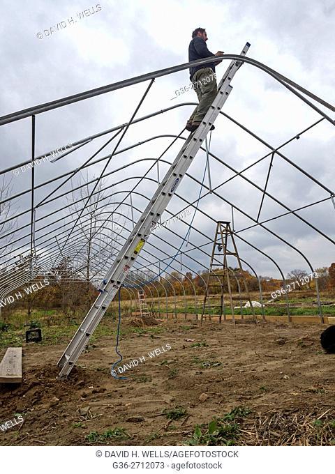 Small-scale farmer builds greenhouses frame on an artisanal organic farm in Johnston, Rhode Island, USA