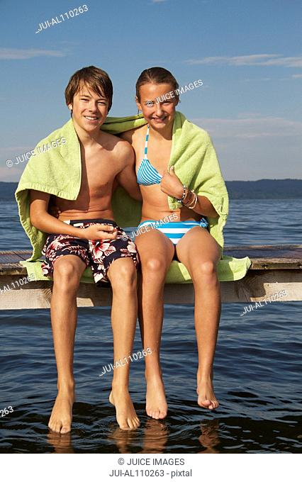 Young teenage couple sitting on pier, smiling, portrait