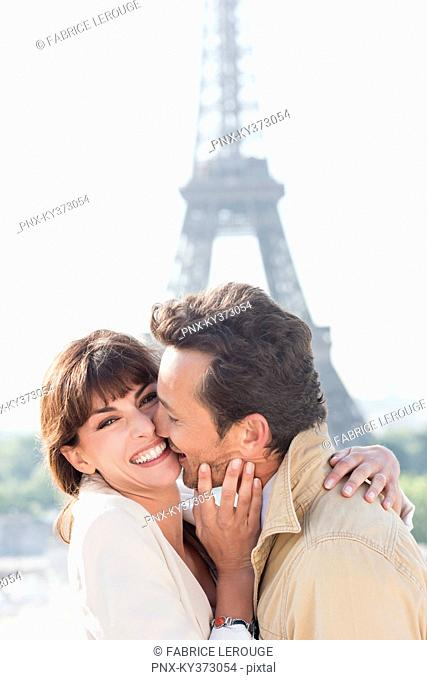 Couple kissing with the Eiffel Tower in the background, Paris, Ile-de-France, France