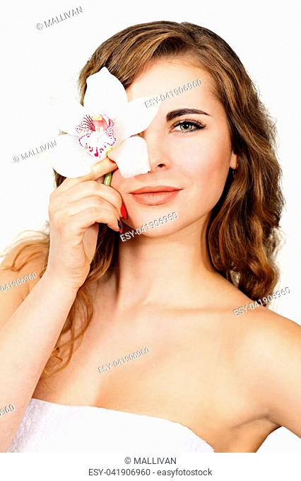 Young beautiful woman holding orchid flower near her eyes