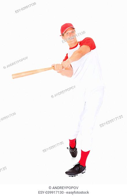 Portrait Of Player Swinging With Baseball Bat Over White Background