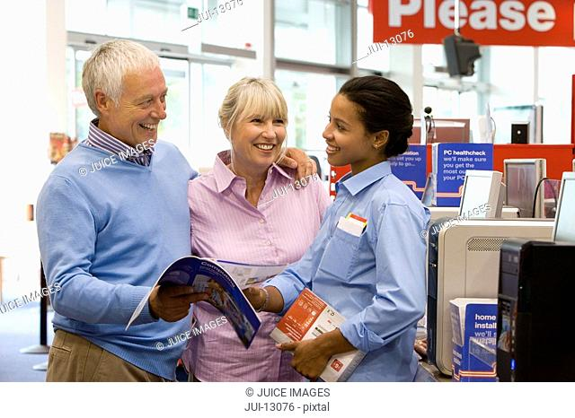 Mature couple shopping for computer, in conversation with saleswoman, smiling